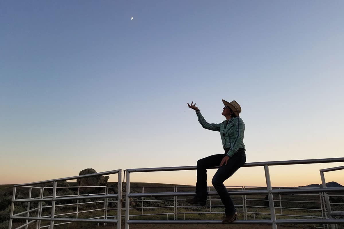 girl holding the moon blue sky sage big piney wyoming cowgirl magazine